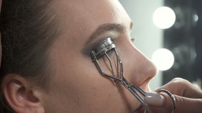 Video of visagist using eyelash curler. In beauty studio stock video footage