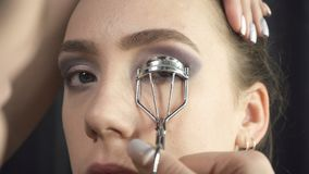 Shooting of master using eyelash tongs. Video of visagist using eyelash curler in beauty studio stock video footage