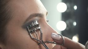 Shooting of visagist using eyelash curler. Video of visagist using eyelash curler in beauty studio stock video footage