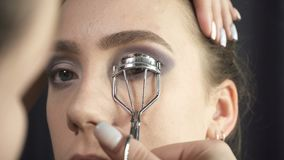 Visagist using eyelash tongs in beauty studio. Video of visagist using eyelash curler in beauty studio stock video footage