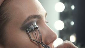 Video of visagist using eyelash tongs. Video of visagist using eyelash curler in beauty studio stock footage
