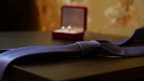 Video wedding rings and a blue tie on the table. Video wedding rings and a blue tie on table stock video