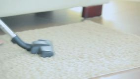 Video of woman hoovering rug