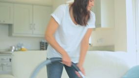 Video of woman standing at the living room hoovering stock footage