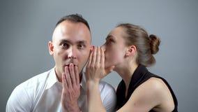 Video of woman talking secret on grey background. Video of man and woman sitting near on grey background stock video