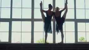 Beautiful young ballerinas dance against the background of a panoramic window. Beautiful silhouettes of ballerinas at a stock footage