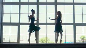 Beautiful silhouettes of ballerinas at a window in studio of the ballet. Beautiful female ballet dancer on a blue. On this video you can see as ballerinas stock footage