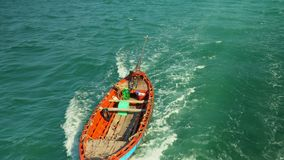 The small fishing boat floats on turquoise water the top view. Adventure background. Vietnam. On this video you can see as the boat tied to the barge floats on stock video footage