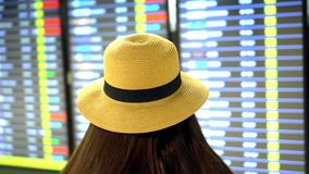 Aroport. The girl with long dark hair with a straw hat checks embarkation of the airplane. The traveler costs a back to. On this video you can see as the girl stock video