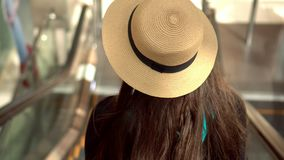 The girl with long beautiful hair goes down on the escalator at the airport. The girl corrects a straw hat. Lovely girl. On this video you can see as the girl stock video