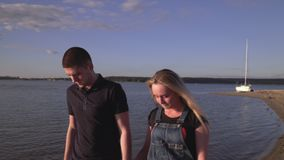 Lovely couple have a rest on the beach. The loving couple walks on the river bank. Beautiful couple.. stock video