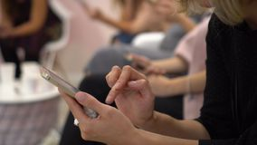 Closeup shot of female hands holding smartphone, typing text on touch screen. Women sit at a conference with phones