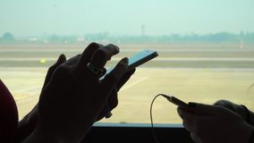 Close-up shot of female hands texting in messenger or typing sms on smart phone by the airport window. Two girls stand. On this video you can see as the woman stock footage