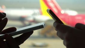 Close-up shot of female hands texting in messenger or typing sms on smart phone by the airport window. Boarding plane in. On this video you can see as the woman stock footage