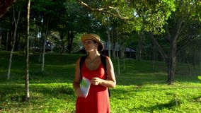 The woman costs against sunshine. The woman in a straw hat on the island in a tropical garden. The smiling woman with stock footage