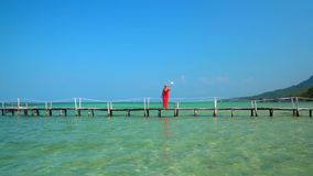 Selfie stick. The woman walks on a pier with Selfie stick. Slow mothion. A pretty lady shoots a video of herself with an. On this video you can see as the woman stock footage