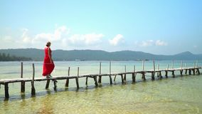The woman in a straw hat goes on a pier on turquoise water. A beautiful landscape on the beach. White tropical sand. On this video you can see as the woman in a stock video footage