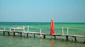 The woman in a red dress and a hat walks on a long wooden pier.Slow mothion. The woman in a straw hat. On this video you can see as the woman in a red dress and stock footage