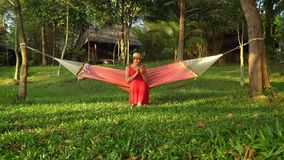 The woman in a straw shlyama and in a red dress sits on a hammock in the middle of a glade. The girl looks in the stock video