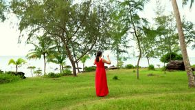 A privacy with the nature. Beautiful Woman in Red Dress Walking in Tropical Garden. The woman in a long red dress walks. On this video you can see as the woman stock footage