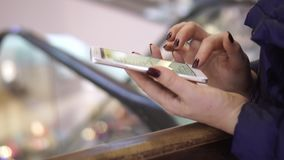 Close-up view of female hands holding smartphone, using the touchscreen technology. Woman spending time in shopping mall. On this video you can see as the woman stock video