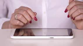 The woman in a white shirt watches information on the tablet. The businesswoman works at office or at home. Typing on. On this video you can see as the woman stock video footage