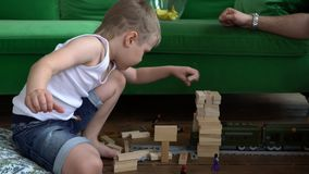 On this video you can see as the young family plays at home on a floor wooden tower. The family plays. The close-knit. The family plays wooden tower. The close stock video footage