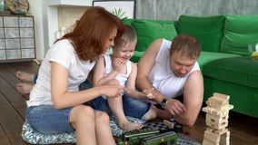 On this video you can see as the young family plays at home on a floor wooden tower. The family plays wooden tower. The. The family plays wooden tower. The close stock video