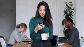 Young indian business woman entrepreneur sending messages with mobile phone in the office.