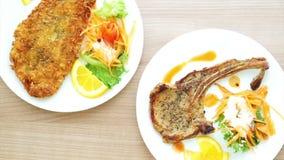 Video zerschlug Fischsteak und grillte Schweinekotelettsteak mit dem Knochen bunter Salat und Gemüse stock footage