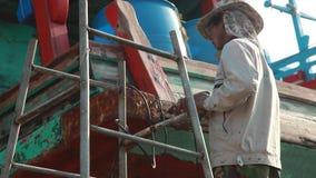 Videoaufnahmen-auf Lager thailändischer Arbeitskraft-Hafenarbeiter, der Boot repariert stock footage
