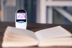 Videobabymonitor met beeld van slaapbaby op het scherm op de lijst met open boek De moeder ontspant tijd tijdens kind dags stock fotografie