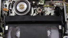 Videoband in i videobandspelaren arkivfilmer