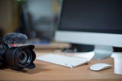 Videobearbeitungsarbeitsplatz mit Videokamera dazu Stockfotografie