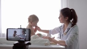 Videoblog, blogger woman medic recording live tutorial video on mobile phone during medical examination of child for. Videoblog, popular blogger woman medic stock footage