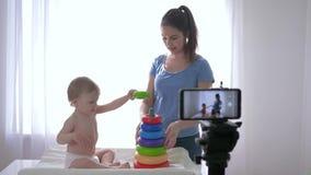 Videoblog, dziecięca chłopiec z kobietą bawić się edukacyjnymi zabawkami i magnetofonowym ogólnospołecznym medialnym wideo w lać  zbiory wideo