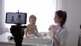 Videoblog, fêmea do médico com estetoscópio escuta a pulsação do coração e a respiração do menino infantil paciente durante o tre vídeos de arquivo