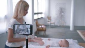 Videoblog, mãe nova usa o telefone celular e faz exercícios para sua filha pequena que encontra-se na tabela em mudança video estoque