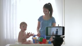 Videoblog streaming live, cute baby boy with mom played by educational toys and filming new episode for vlog in stock footage