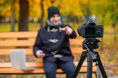 Videobloger leads his report on his camera background blur Royalty Free Stock Image