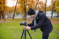 The videoblogger adjusts his camera in the park. Videobloger in a black jacket and hat looks at the camera in the fall in the park Stock Photos
