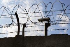 Videocamera di sicurezza dietro il recinto del filo spinato intorno alle pareti della prigione Fotografia Stock Libera da Diritti
