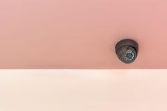 Videocamera di sicurezza moderna sul muro di cemento dell'interno Fotografia Stock
