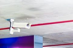 Videocamera di sicurezza moderna sul muro di cemento dell'interno Immagine Stock