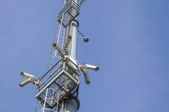 Videocamera di sicurezza sull'alta torre del palo del sistema del CCTV di giorno Immagini Stock