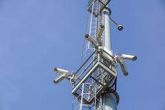 Videocamera di sicurezza sull'alta torre del palo del sistema del CCTV di giorno Fotografia Stock