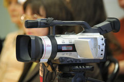 Videocamera at press conference. On a background of journalists. The background is washed away Royalty Free Stock Image