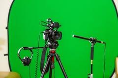 Videocamera su un treppiede, sulle cuffie e su un microfono direzionale su un fondo verde La chiave di intensità Schermo verde fotografia stock libera da diritti