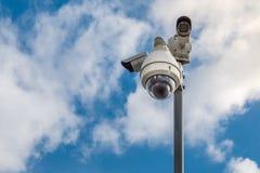 Videocamere di sicurezza del CCTV sul palo su cielo blu con il fondo bianco delle nuvole fotografia stock libera da diritti