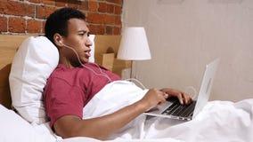 Videochat für Arbeit durch den jungen afrikanischen Mann, der im Bett nachts liegt stock footage